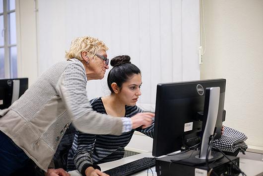 Professorin erklärt einer Studentin etwas am Computer