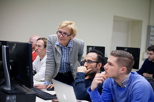 Professorin mit Studenten an einem Computer